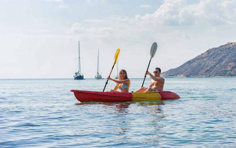 Couple exploring calm tropical bay by kayak.