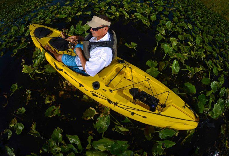 man kayak fishing in lily pads in yellow kayak